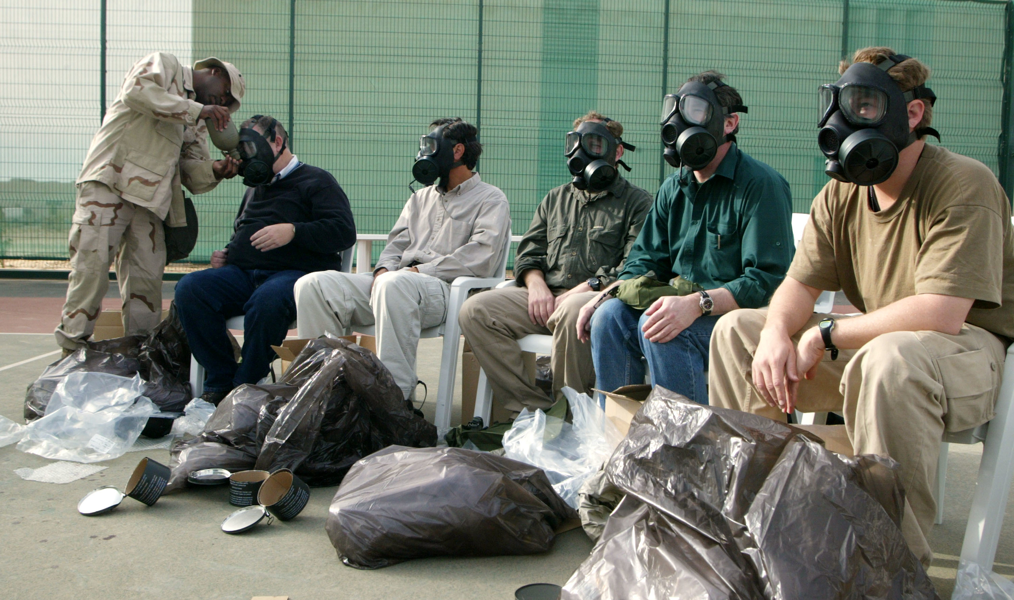 A soldier fits Western journalists with gas masks before the 2003 invasion of Iraq. More than 600 journalists were embedded in military units. (Photo: Joe Raedle / Getty)