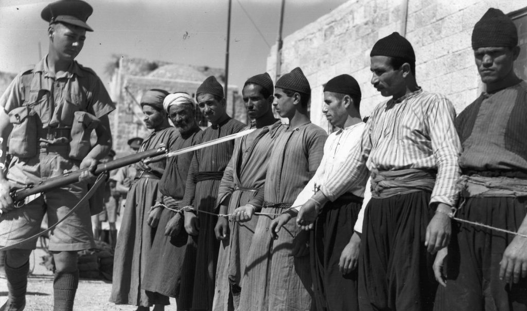 A British soldier guards Palestinian prisoners in Jerusalem, 1938 (Photo: Fox Photos / Getty)